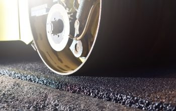 Thin layer of new asphalt close-up and road roller